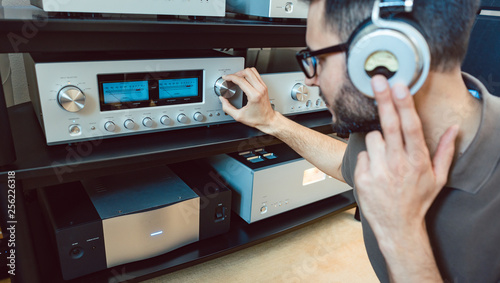 Photo Man turning up the volume on home Hi-Fi stereo