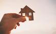 Leinwanddruck Bild - Man's hand holds wooden flat house against the sun