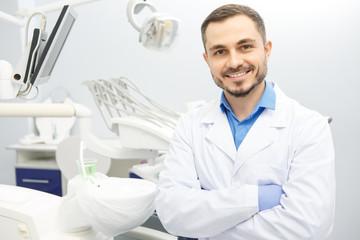 Przystojny męski fachowy dentysta przy jego biurem