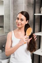 Happy Brunette Woman Brushing Hair While Standing In Bathroom