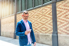 Mature Man Walking Along The Street While Using His Smarphone Against A Bricked Wall