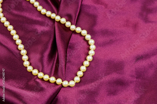 Foto  Pearl necklace on purple satin fabric background