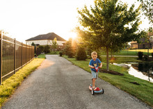 Boy Riding Push Scooter On Road During Sunset