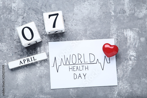 Fotografia  Text World Health Day with red heart and cube calendar on grey background
