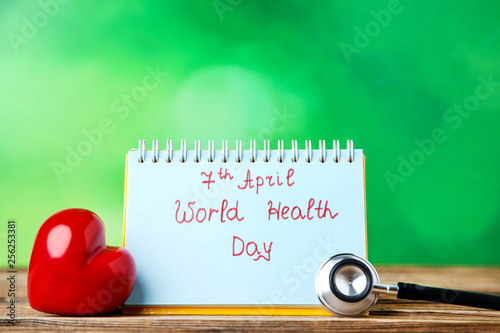 Fotografía  Text World Health Day with stethoscope and red heart on green background