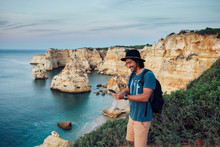 Smiling Man Using Phone While Standing On Cliff By Sea