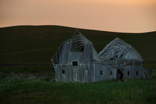 Abandoned Barn On Grassy Field Against Clear Sky During Sunset