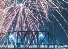 Low Angle View Of Firework Display Over Bridge In Sky