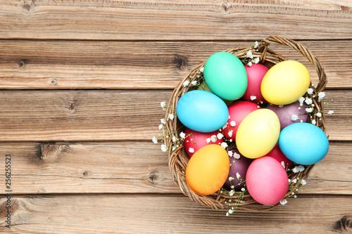 Fotografie, Obraz  Easter eggs in basket with gypsophila flowers on wooden table
