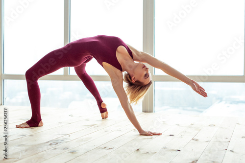 Foto  Peaceful good-looking woman using her body flexibility for extreme stretching