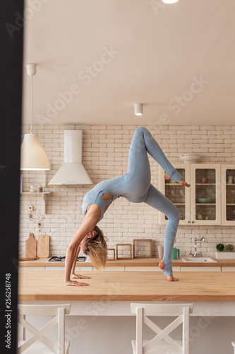Fotografiet  Flexible and elastic female gymnast being extremely powerful and strong
