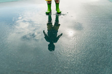 Reflection Of Boy In Rubber Boots Standing In Puddle