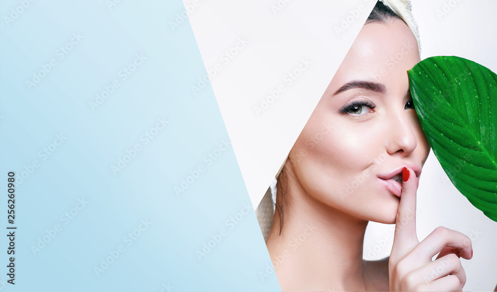 Fototapety, obrazy: Portrait of young beautiful woman with healthy glow perfect smooth skin holds green tropical leaf, look into the hole of colored blue paper. Model with natural nude make up. Fashion, beauty, skincare.