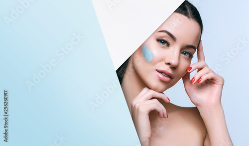Portrait of beautiful woman with healthy glow perfect smooth skin look into the hole of blue paper. Young girl enjoys cream facial mask. Fashion, beauty, skincare, cosmetology concept.