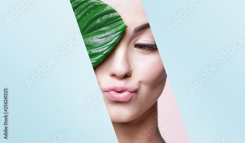 Portrait of young beautiful woman with healthy glow perfect smooth skin holds green tropical leaf, look into the hole of colored blue paper. Model with natural nude make up. Fashion, beauty, skincare.