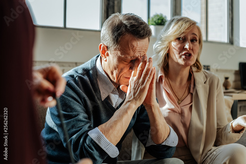Fotografiet  Distressed old man being depressed with situation in his family
