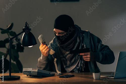 Fotografía Criminal in black mask holging pistol and looking at handset