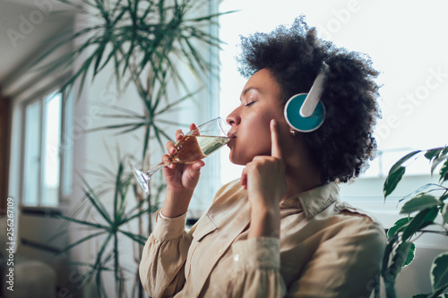 Foto  Young beautiful african american woman relaxing and listening to music using headphone, drinking wine