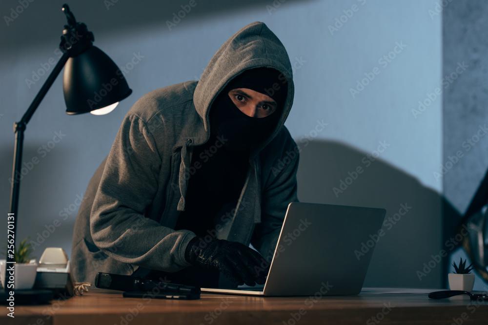 Fototapeta Burglar in mask and gloves typing on laptop keyboard in dark room
