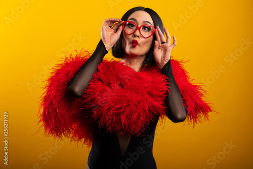 Valokuva  Beautiful Asian woman with vibrant red feather boa and heart shaped glasses,