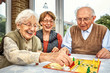 canvas print picture - Elderly couple and daughter playing board game