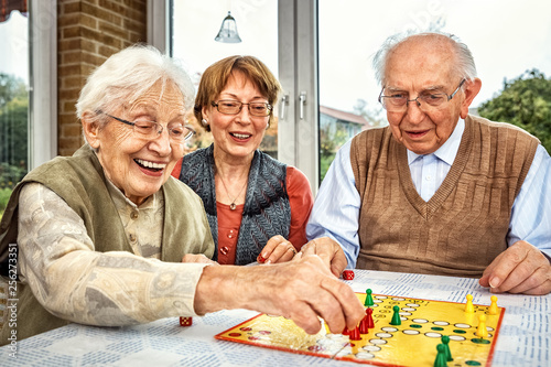 Elderly couple and daughter playing board game - 256273351