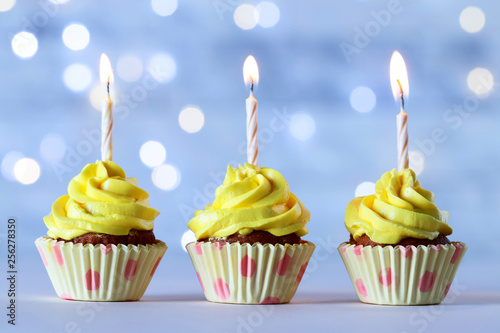 Fotografie, Obraz  Delicious birthday cupcakes with burning candles on wooden table against blurred