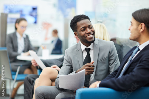 Portrait of young African businessman talking to colleagues sitting on sofa in o Canvas Print