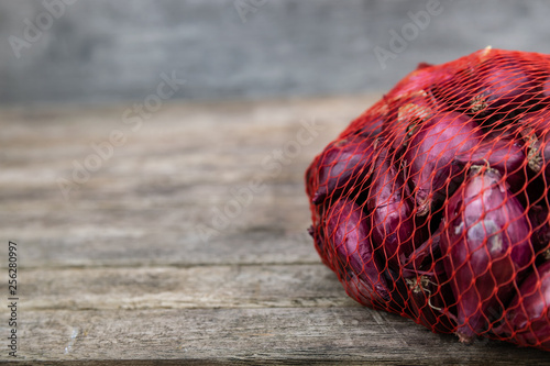 Fotomural  Farming,cultivation, agriculture and vegetables concept: small red onion in a plastic netting bags,prepared for planting in the garden on a wooden table