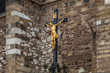 The gilded crucifix of Christ in the courtyard of the sabor Peter and Paul in the city of Brno (Czech Republic)