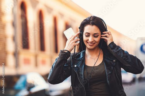 Young woman enjoys music on the street - 256283554