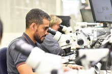 Man Using A Microscope For The Quality Control In The Manufacturing Of Circuit Boards For The Electronics Industry