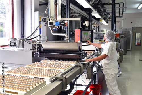 Fotografía Arbeiterin am Fliessband in der Lebensmittelindustrie - Produktion von Pralinen