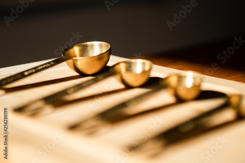 Fotografía  Golden kitchen scoops arranged in a line on a wooden chopping board
