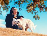 Fototapeta Zwierzęta - Perros graciosos. Golden retriever. Mujer joven y sus mascotas pasando un rato divertido al aire libre