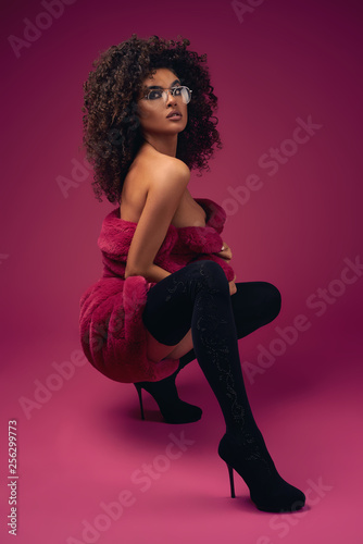 Valokuva  Half naked model in a fur coat and boots sitting on a bright background