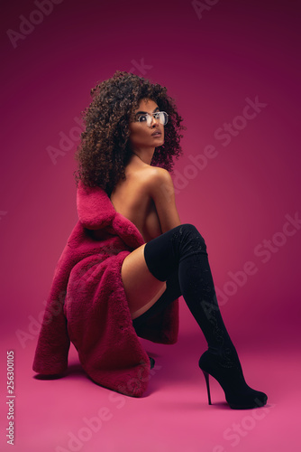 Half naked model in a fur coat and boots sitting on a bright background Tapéta, Fotótapéta