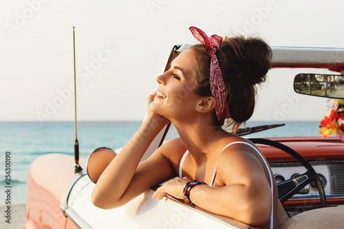 Piękna i szczęśliwa kobieta wśrodku retro kabrioletu samochodu
