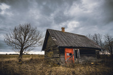 Old Abandoned Wooden House With Red Door In A View Of Dark Cloudy Sky.
