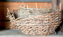 Two Vintage Woven Baskets Inside Each Other On A Dusty Wooden Shelf