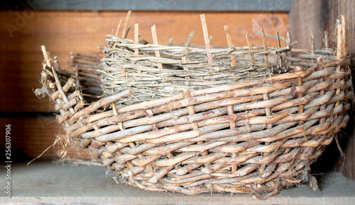 two vintage woven baskets inside each other on a dusty wooden shelf Canvas Print