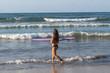 Mujer surfeando en playa de Sayulita, México.