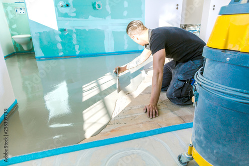 Fotografía  Plasterer during floor covering works with self-levelling cement mortar