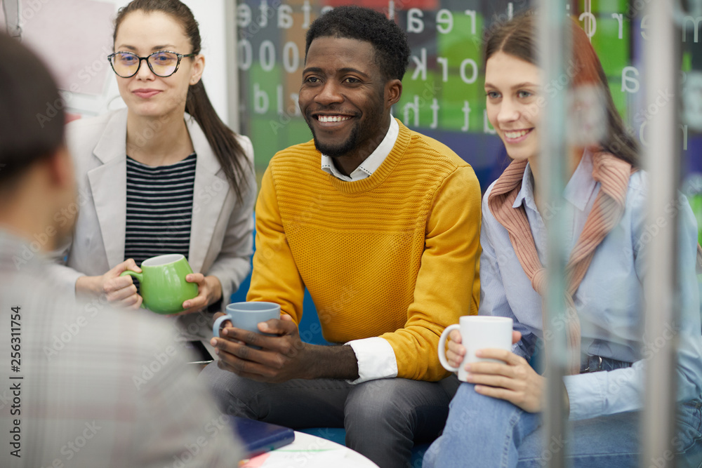 Fototapety, obrazy: Multi-ethnic group of business people dressed in casual wear chatting in break room