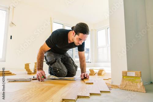 Obraz Handwerker bei der arbeit, fischgrät parkett verlegen  - fototapety do salonu