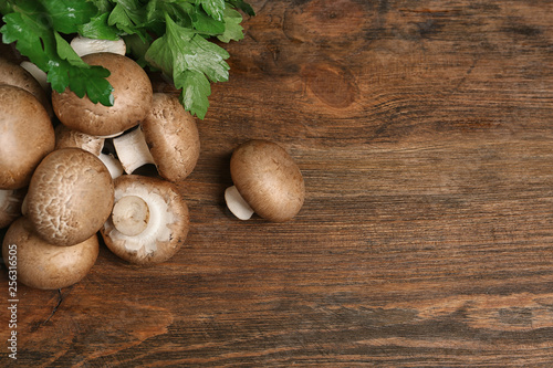 Fotografía  Fresh champignon mushrooms on wooden background, top view with space for text
