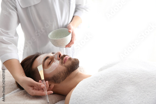 Cosmetologist applying mask on client's face in spa salon