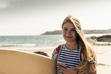Young Woman On The Beach, Carrying Surfboard