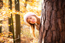 Young Girl Behind Tree In Autumn