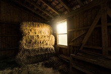 Traditional Farm Barn With Bales Of Straws And Light Coming Through Window